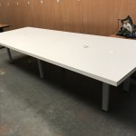 White rectangular boardroom table with comms
